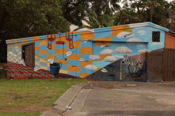 Ida Lawrence & Caitlin Hespe. Mural #1, Housepaint on garage wall, 36th Battalion Park 2010. side view