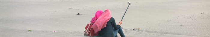 A photograph of the backs of two young Indonesian women, both wearing head scarves, and wielding a camera on a selfie stick